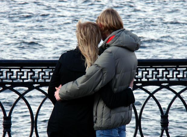 влюбленные в осенних куртках стоят в обнимку на красивой набережной реки