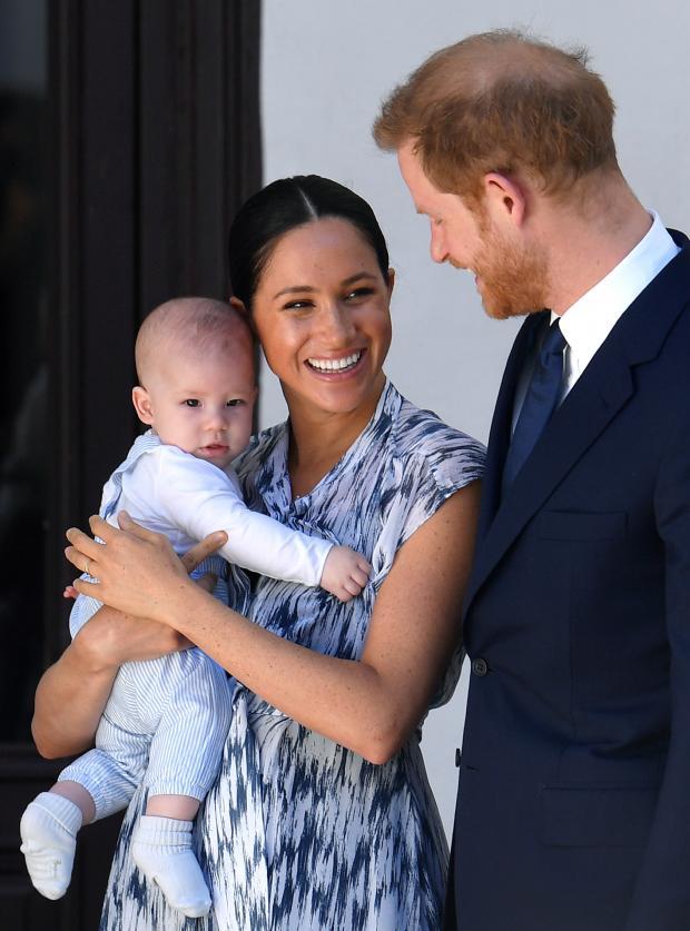 Меган в черно-белом платье с сыном на руках