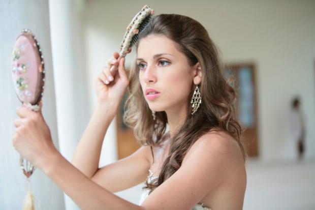 красивая женщина расчесывается перед ручным зеркалом