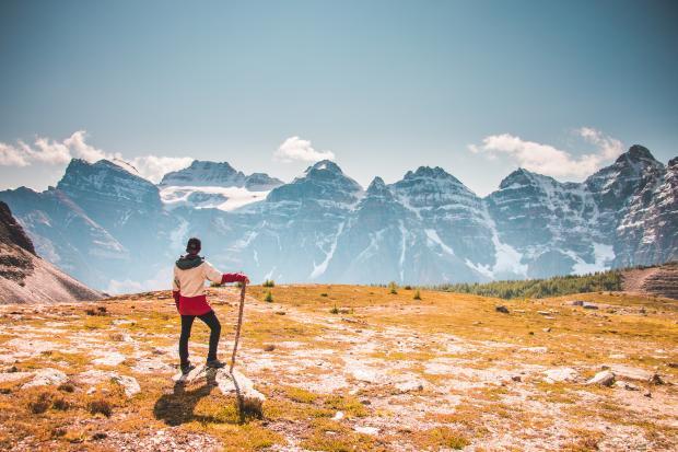 Молодой человек стоит на фоне гор