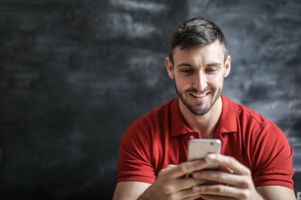 Мужчина в красной футболке пишет сообщение на телефоне