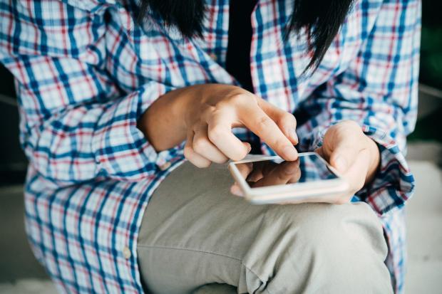 Девушка в клетчатой рубашке пишет сообщение на телефоне
