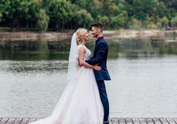 Жених и невеста стоят возле реки
