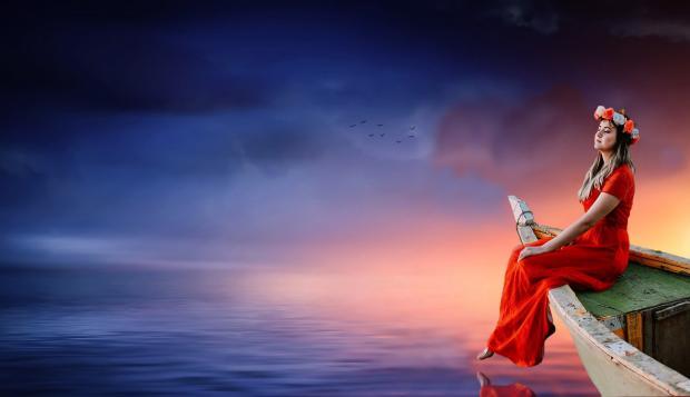 девушка в красном платье и венке сидит на носу лодки