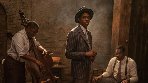 Чедвик в полосатом костюме и шляпе вместе с музыкантами