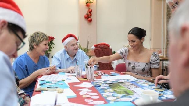 Беременная Меган Маркл за столом во время выполнения королевских обязанностей