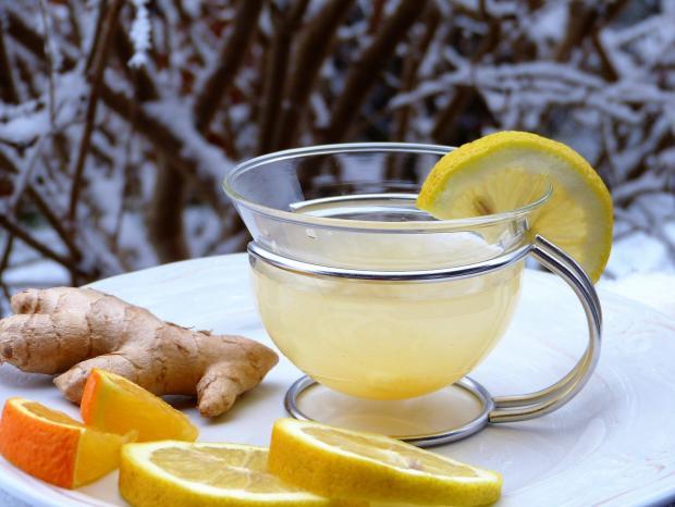 напиток с лимоном и имбирем в чашке на снегу