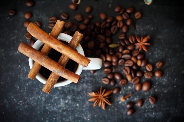 палочки корицы на белой чашке с кофе рядом с кофейными зернами