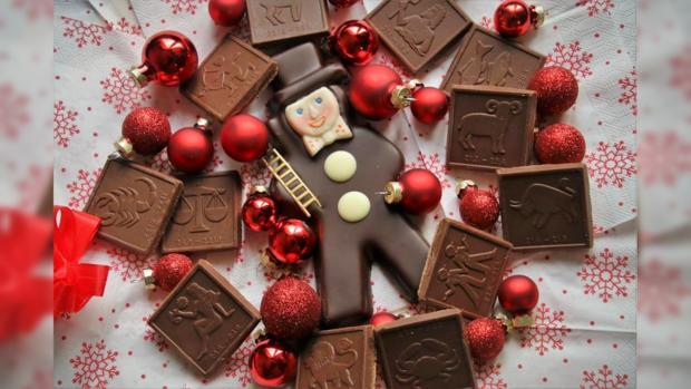 на столе лежат шоколадные знаки Зодиака и новогодние игрушки