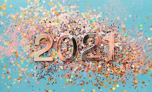цифра 2021 на фоне разноцветных блесток на голубом фоне