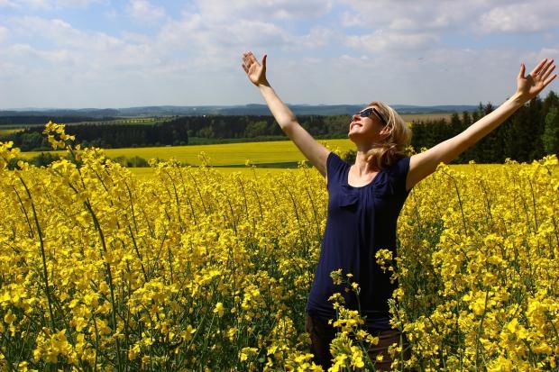 красивая девушка стоит в поле с желтыми цветами с поднятыми к небу руками