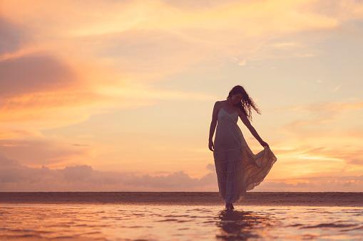 женщина на закате идет по берегу моря
