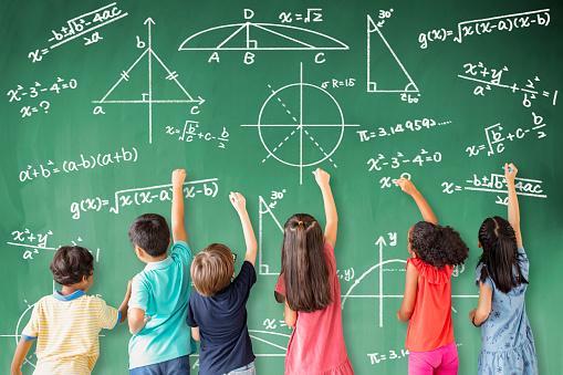 стоящие у доски с математическими формулами дети