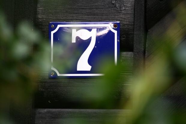 прибитая на деревянный дом табличка с номером 7