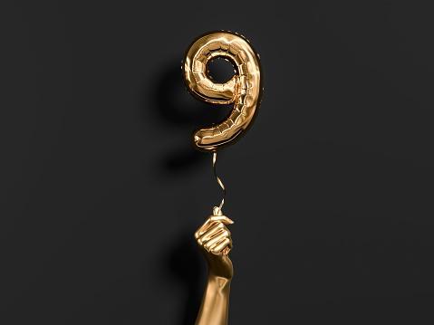 рука держит воздушный шар в виде 9 золотого цвета