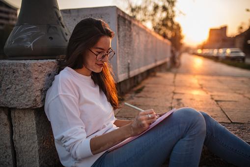 сидящая на мостовой девушка записывает свои мысли на бумагу
