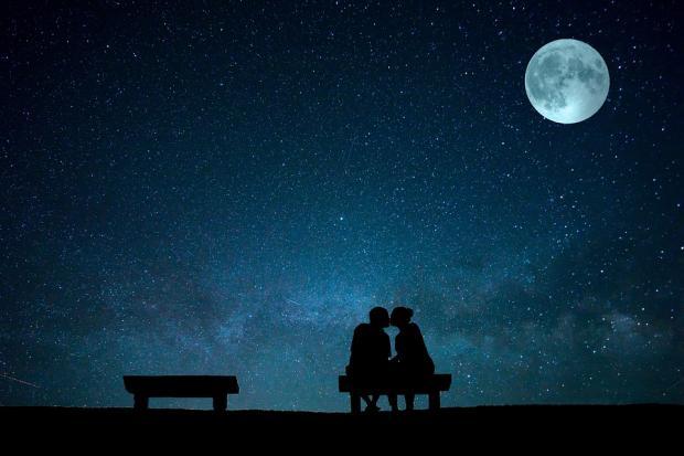 фигуры влюбленных на скамейке под ночным лунным небом