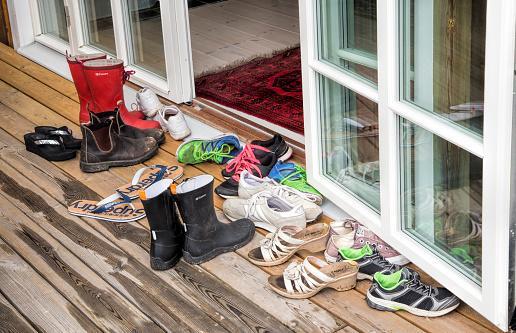 много обуви стоит на полу перед входом в дом