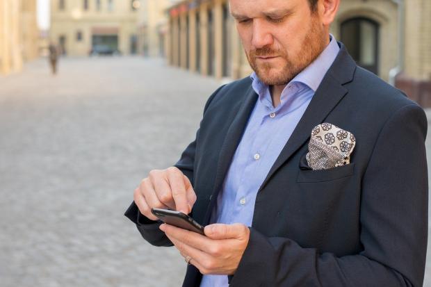 элегантно одетый мужчина с телефоном в руке