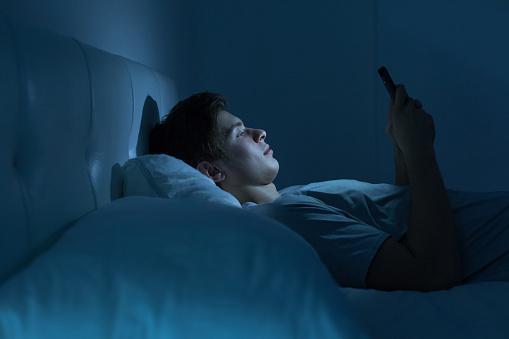 лежащий в постели мужчина смотрит на экран телеофна