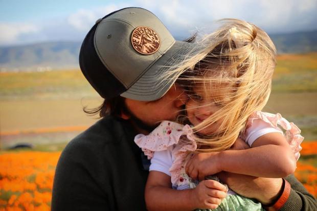 Натан в кепке целует дочь в щеку