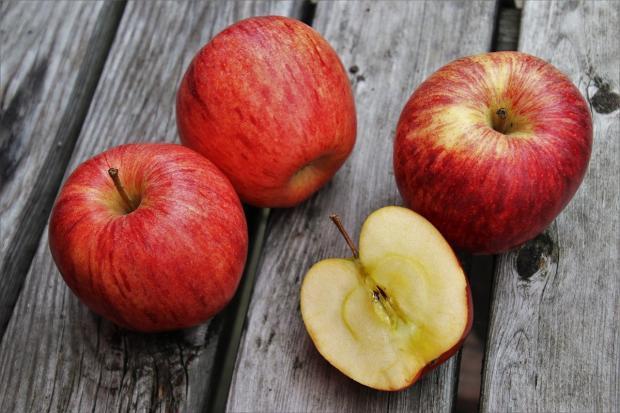 красные яблоки лежат на деревянной скамейке