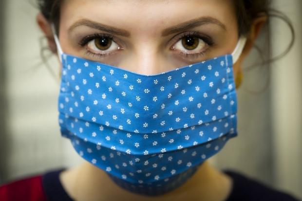 девушка в голубой маске в горошек от коронавируса