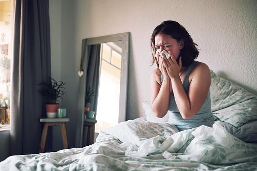заболевшая простудой женщина сидит в кровати