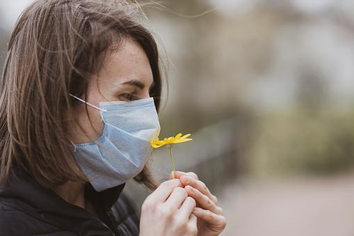 девушка в защитной маске нюхает желтый цветок