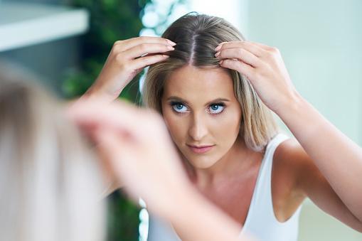 девушка перед зеркалом рассматривает свои волосы на голове