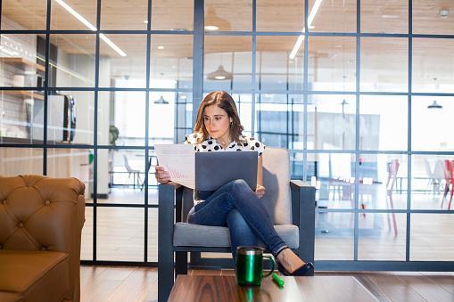 девушка в просторном помещении сидит в кресле с ноутбуком
