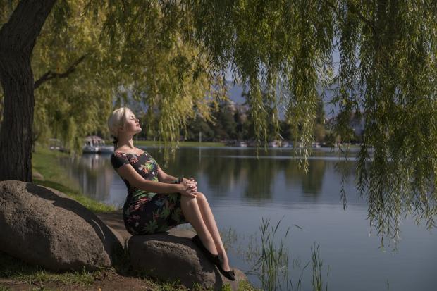 стройная девушка сидит в раздумьях на валуне у реки