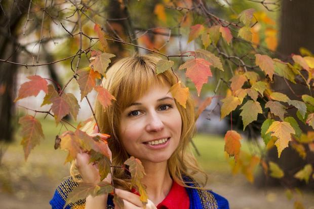 улыбающаяся девушка на фоне осенних ветвей