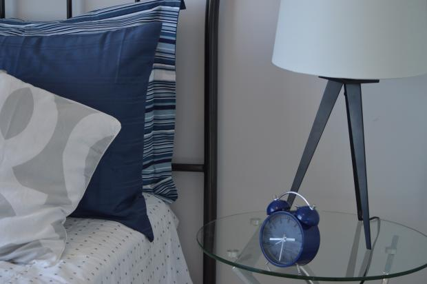 синий механический будильник стоит на прикроватном стеклянном столике