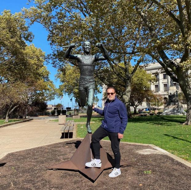Арнольд позирует у статуи бегуна