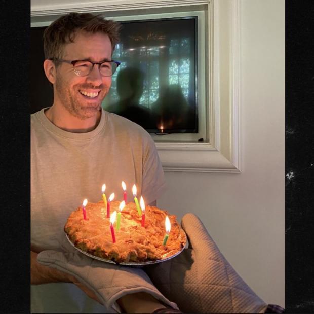 Актер улыбается перед тем как задуть свечи на пироге