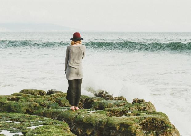 девушка стоит на утесе у бушующего моря