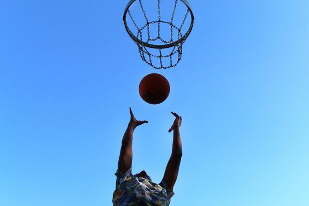баскетболист бросает мяч в корзину