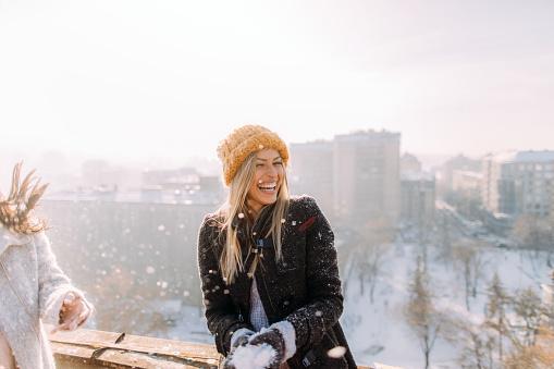 смеющаяся девушка играет зимой в снежки