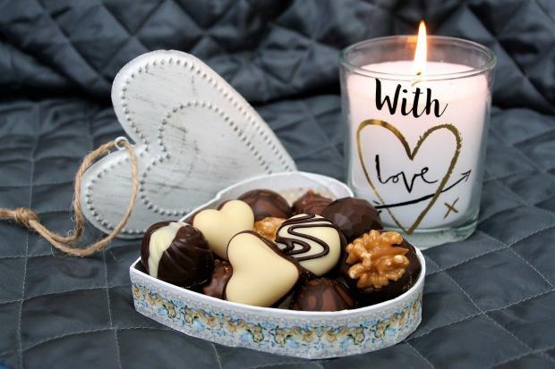 горящая сувенирная свеча и конфеты в коробке в форме сердца