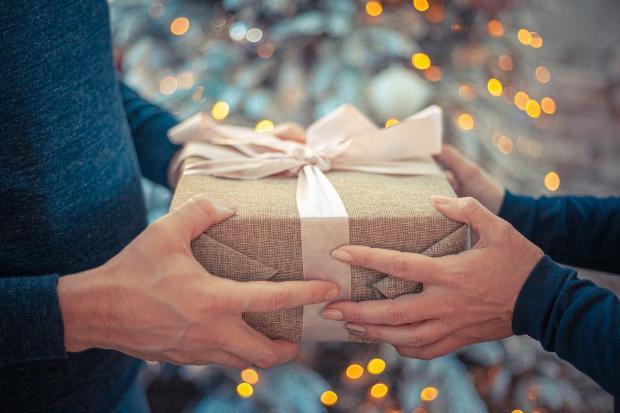 перевязанный розовой ленточкой подарок передается из рук в руки