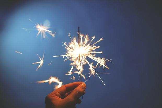 горящий в руке бенгальский огонь на фоне ночного неба