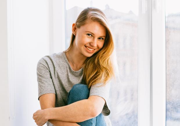 Блондинка сидит на подоконнике и улыбается