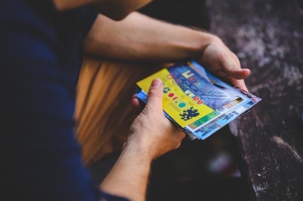 Мужчина держит в руках лотерейные билеты