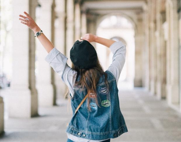 Девушка в джинсовой куртке идет по дороге