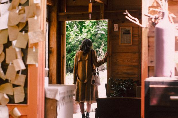 Длинноволосая девушка в коричневом пальто стоит в дверях