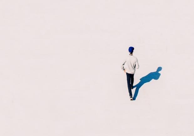 Мужчина идет по белому песку