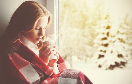 сидящая у окна девушка пьет кофе
