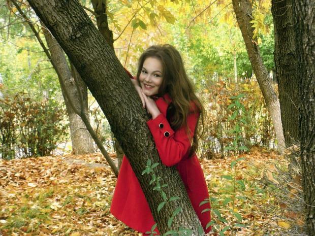 улыбающаяся девушка в красном пальто обнимает ствол осеннего дерева