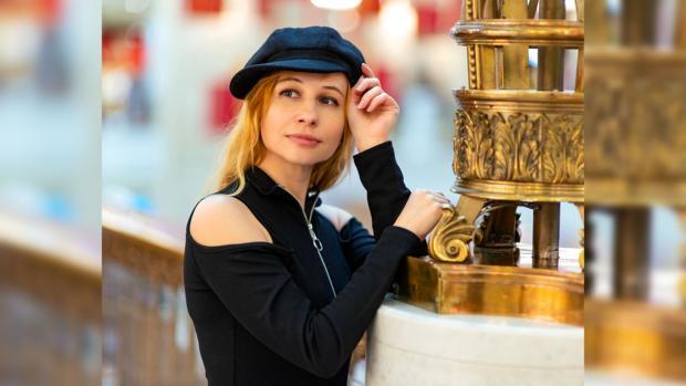 девушка в черном джемпере и кепке стоит на набережной рядом с перилами
